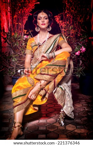 Indian beautiful girl sitting in in a yellow sari and jewelery with pearls,looks like royalty - stock photo