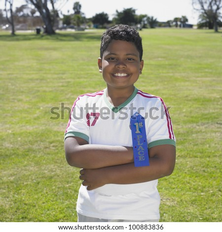 Indian boy smiling with blue ribbon outdoors