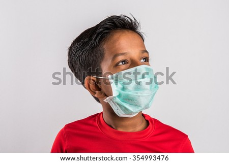 indian boy wearing face mask, Flu illness child boy in medicine healthcare mask, A Little indian boy with the protective mask, boy with brown skin wearing medical mask - stock photo