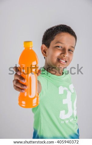 indian boy with cold drink bottle, asian boy drinking cold drink in pet bottle, small boy and cold drink, indian cute boy drinking mango juice or orange juice in plastic bottle - stock photo