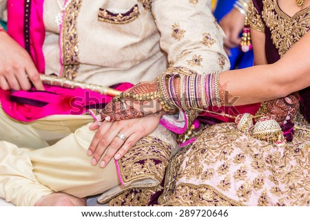 Indian bride and groom in a temple during wedding ceremony. Rings exchanging. - stock photo