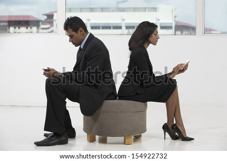 Indian business colleagues using smart phones. Indian businesspeople with cell phones. - stock photo
