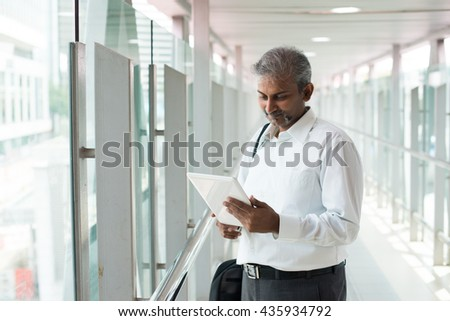 indian business executive working on tablet computer in office with copyspace on left