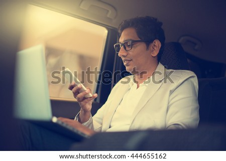 indian business male using laptop inside the car - stock photo