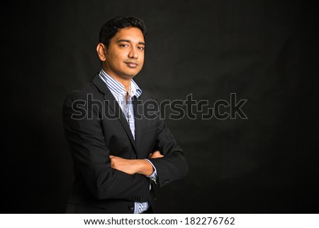 indian business man on dark background, crossed arm  - stock photo