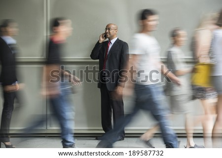 Indian Business man using a Cell Phone with People walking past in a rush. - stock photo