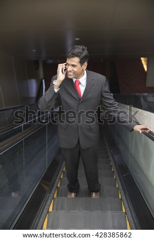 Indian business Man using his Smart phone while standing on an escalator in the city.