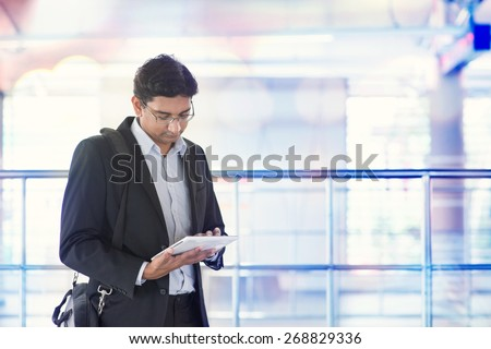 Indian business man using tablet computer while waiting train at railway station. - stock photo