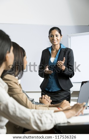Indian business woman giving a presentation for her business colleagues. - stock photo