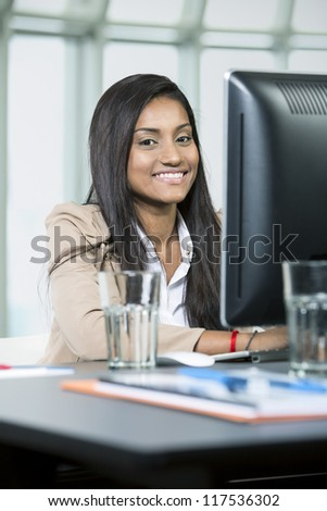 Indian business woman in office working on her computer - stock photo