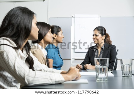 Indian business woman sitting talking with her colleagues in a meeting - stock photo