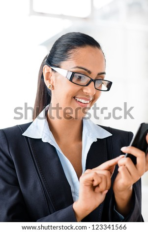 Indian business woman using mobile phone happy - stock photo