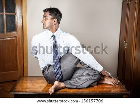 Indian businessman doing yoga on the table in the office  - stock photo