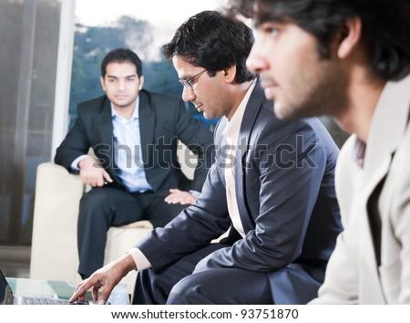 indian businessman explaining on laptop in meeting - stock photo