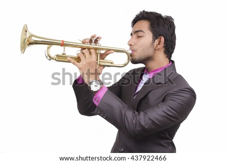 Indian businessman in a suit plays on a trumpet