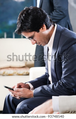 indian businessman sending or reading sms on his mobile phone with his colleague in the background