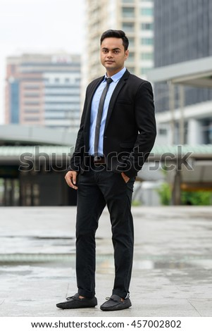 Indian businessman standing full length shot outdoors - stock photo