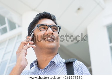 Indian businessman talking on phone in front modern office building. - stock photo
