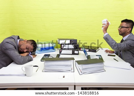 Indian businessman throwing paper at his sleeping twin - stock photo