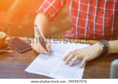 Indian Businessperson Signing Contract,Man writing paper at the desk, man writing with pen and reading books at table,man Signing, Contract, Forms. in office ,morning light ,selective focus. - stock photo