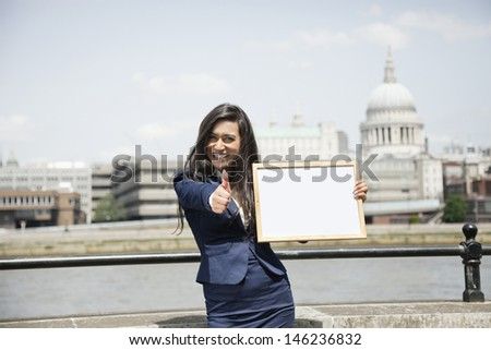 Indian businesswoman gesturing thumbs up as she holds a sign with St. Paul's Cathedral in background