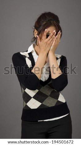 Indian businesswoman peeking through fingers - stock photo