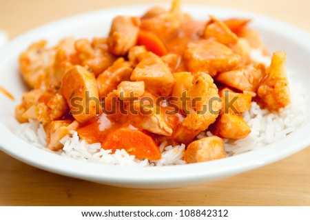 indian butter chicken with carrots and cauliflower over white rice - stock photo