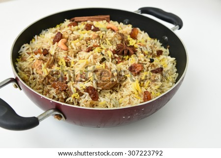 Indian Chicken Biryani/Biriyani or fried rice with chicken leg or drumstick in a pan on a white background .closeup view of delicious chicken pulao or pilaf with colorful garnish. Kerala India - stock photo