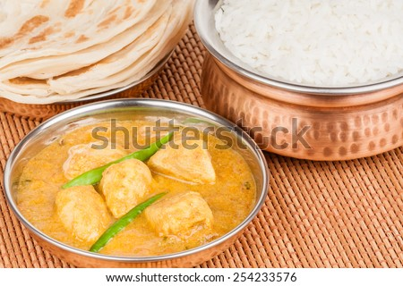 Indian chicken curry meal with rice & parotta (Indian bread) served in authentic copper utensils. Green chilli used as garnish. - stock photo