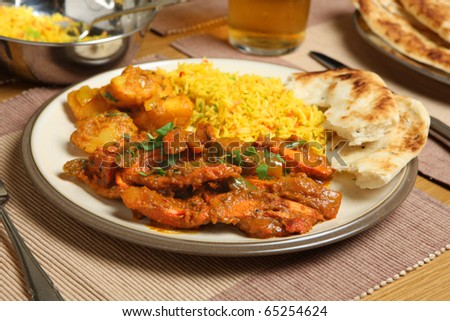 Indian chicken jalfrezi with potato curry, rice and naan bread. - stock photo