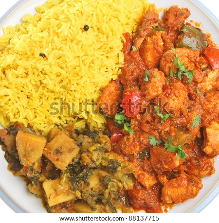 Indian chicken jalfrezi with saag aloo vegetable curry and pilau rice. - stock photo
