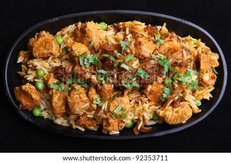 Indian chicken tikka biriyani in a cast iron sizzler dish - stock photo