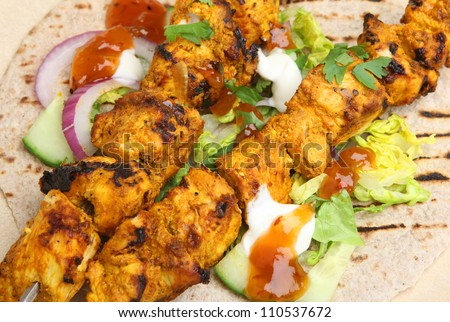 Indian chicken tikka kebabs served with chappati, salad and mango chutney. - stock photo