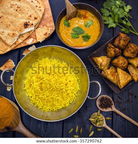 Indian chicken tikka masala curry in balti dish served with pilau rice, plain naan bread, vegetable samosas, and onion bhajis - stock photo