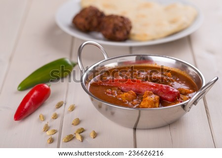 Indian Chicken Vindaloo Curry in Balti Dish with Fresh Chilli Peppers, Cardamom Seeds, Onion Bhajis and Naan Bread - stock photo