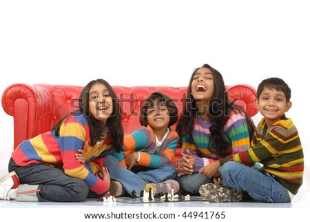 indian children playing board game at home - stock photo