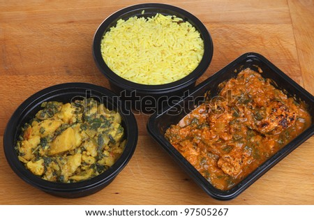 Indian convenience food of chicken massala curry, saag aloo and pliau rice. - stock photo