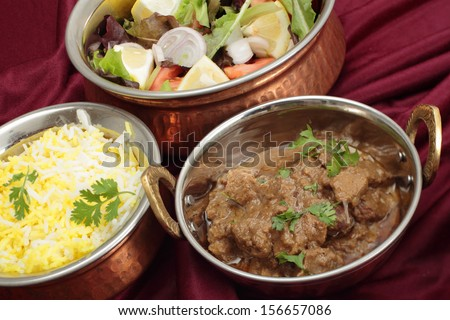 Indian copper dishes with beef rogan josh, white and yellow rice and a salad, shot with a tilt-shift lens to hold focus from front to back. - stock photo