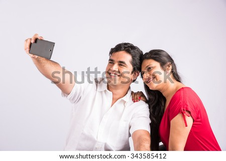 indian couple taking selfie on white background, side view, asian couple and mobile selfie, mobile selfie, couple selfie - stock photo