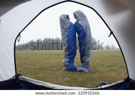 Indian couple wrapped in sleeping bags at campsite - stock photo