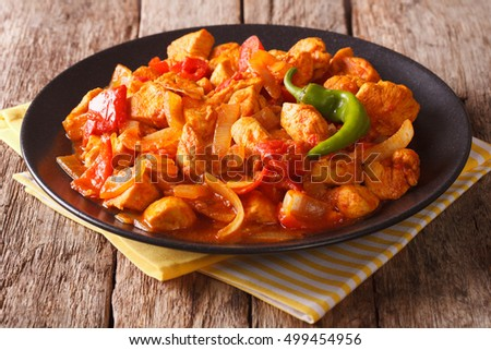 Indian Cuisine: Spicy chicken jalfrezi with pepper and onion close-up on a plate. horizontal