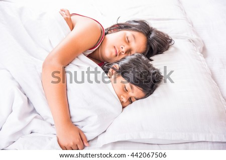 indian cute little siblings or sisters or friends sleeping in a bedroom