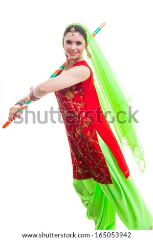 Indian dancer in traditional beautiful green and red dress with veil and sticks