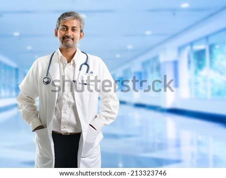 Indian doctor. Mature Indian male medical doctor standing inside hospital. Handsome Indian model portrait. - stock photo