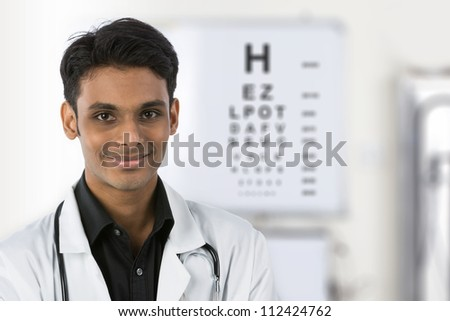 Indian doctor with an eye test chart out of focus in the background. - stock photo