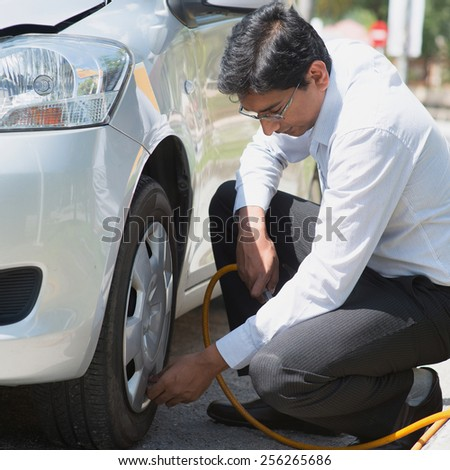 Indian driver checking air pressure and filling air in the tires of his car. - stock photo