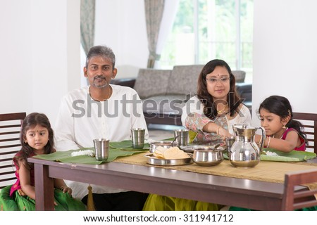 Indian family dining at home. Photo of India people eating rice on dining table. Traditional home cook meal.