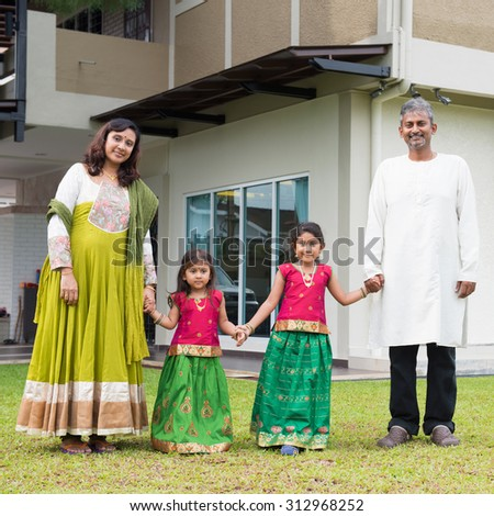 Indian family in traditional dress saree holding hands standing outside their new home. - stock photo