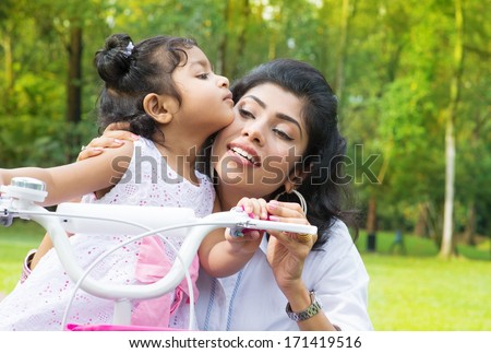 Indian family outdoor activity. Asian Mother teaching daughter cycling at the park in the morning. Child kissing parent. - stock photo