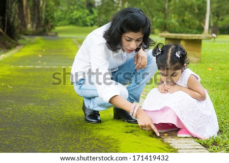 Indian family outdoor activity. Candid portrait of mother and daughter exploring on nature, outdoors education. - stock photo